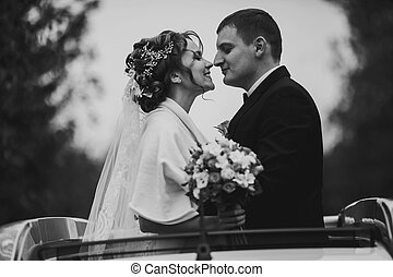 A moment before a kiss of newlyweds standing in a hatchway