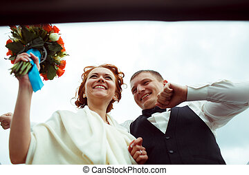 A view from below on a smiling bride and groom standing in a hatchway