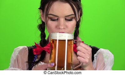 Oktoberfest girl flirting and drinking beer from a glass. Green screen. Slow motion