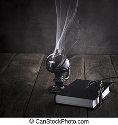 Smoking thurible burning frankincense and bible on table
