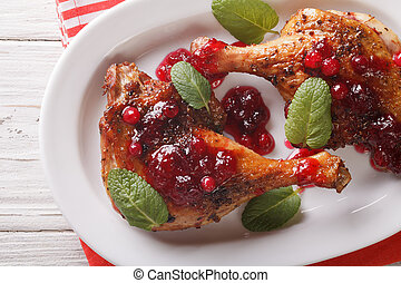 Tasty baked duck leg with cranberry sauce and mint closeup...