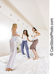 Girls friends jumping on bed - Three pretty young women...