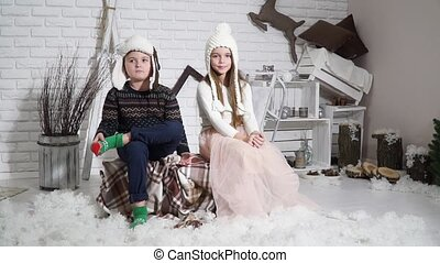 Children sit pose for the camera in the studio