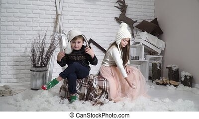 Boy with girl in hats sit on a background of the winter...