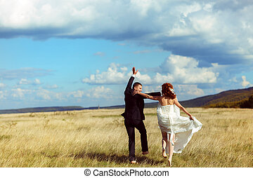 Wedding couple has fun walking along the field in a shiny weather