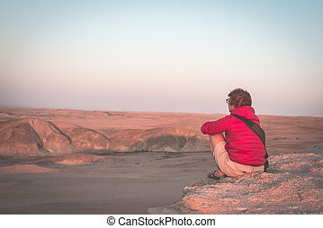 Rear view of woman sitting on rocks and looking at expansive view over the scenic Namib desert at dusk time. Travel in the Namib Naukluft National Park, Namibia, Africa.