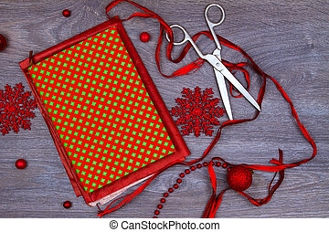 Wrapping up christmas gift. - Notebook, scisors, red bows,...