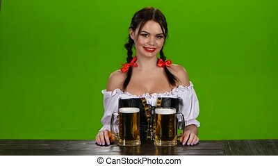 Lady in Bavarian costume offers drink two glasses of beer....