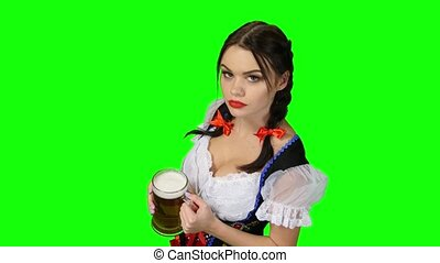 Girl in Bavarian costume offers a glass of beer. Green...