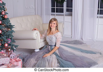Girl in stylish dress sitting on the floor