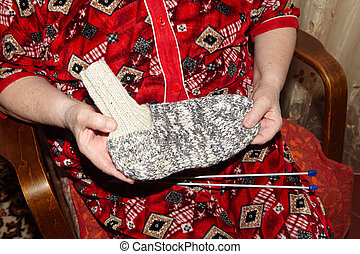 Old woman and knitting clothes