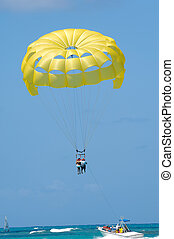 People are parasailing - A couple are parasailing over the...
