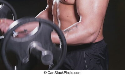 Man doing weight lifting in gym on black background