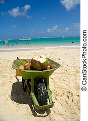 Coconut drink in wheelbarrow on beach - A coconut drink in...