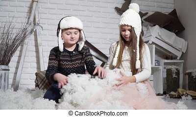 Small children mold snowmen and looking at each other -...