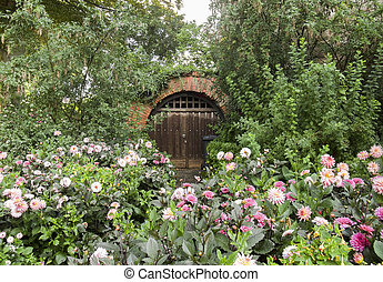 historic cellar entrance surrounded by flowers and other...