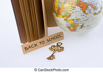 Globe, key and back to school title on a notebook