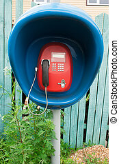 Red payphone in blue booth near to fence