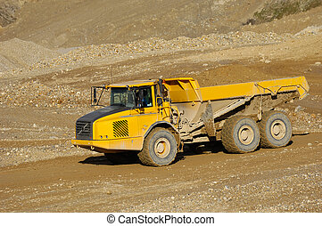 Yellow mining dump truck - A yellow dump truck is driving in...