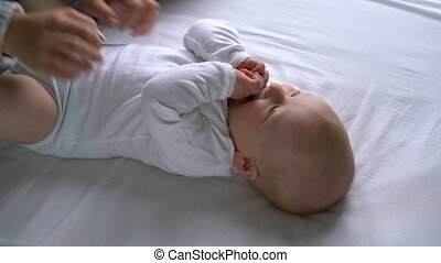 mother tickles the baby and he laughs lying on the bed -...
