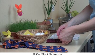 hands put white egg into silk material. Easter eggs...