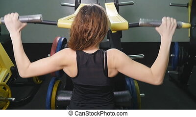 A back view of a trained girl doing exercises. Training for...