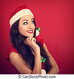 Beautiful thinking smiling woman in santa claus christmas...