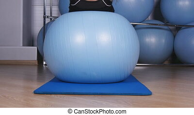 The woman trains on fitball in gym