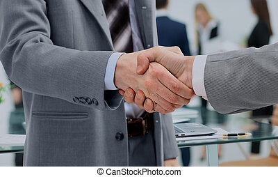 in a sign of cooperation, the partners shake hands after...