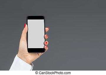 Hand holding mobile smart phone isolated on a gray...