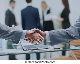 business partners shake hands after a meeting on the...
