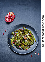 roasted snap green beans with Pomegranate on a black...
