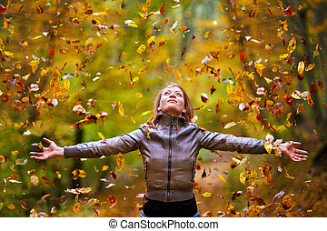 Young lady throwing up leaves - Young woman throwing fallen...