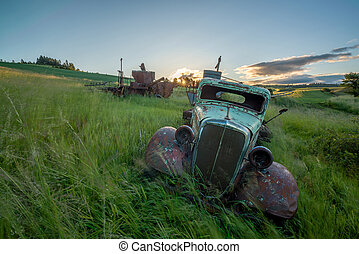 Grasses blow in the wind with rusted old farm truck