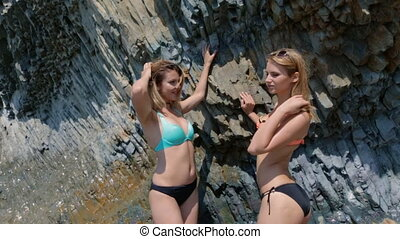 Two models in bikinis moving in the sea near the rocks