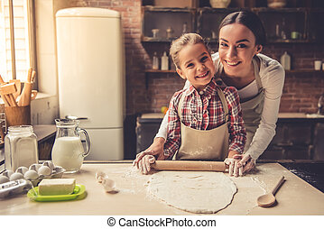 Mom and daughter baking - Cute little girl and her beautiful...