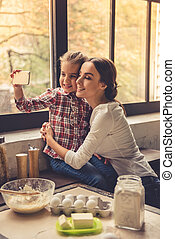 Mom and daughter in kitchen - Beautiful young mom and her...