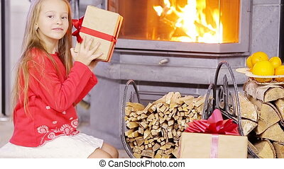 Smiling nice girl opening christmas present near fireplace
