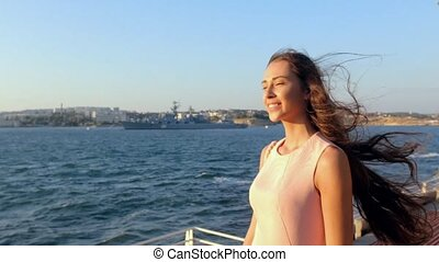 Sensual girl with long hair posing in the park by the sea