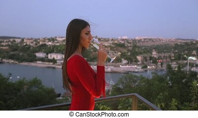 Beautiful young woman drinking champagne from the glass on...