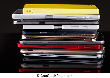 Heap of electronical devices close up - smartphones on black...