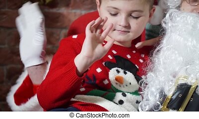 Close-up of a boy and Santa and girl waving their hands -...