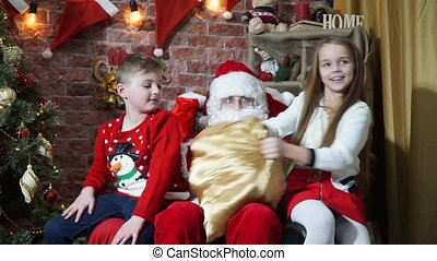 Bad girl and boy with the good behavior of sitting on the lap of Santa Claus