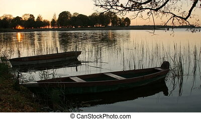 Locked boat by the lake - Two boats on the lake shore,...