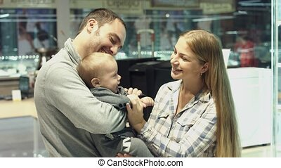 Family with baby son choosing household appliances in the store