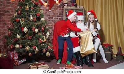 Children have fun take out the gifts from Santa bag -...