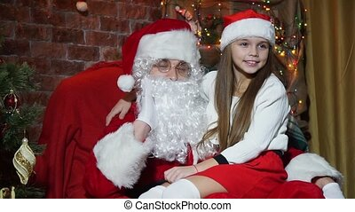 Closeup girl posing sitting on the hands of Santa Claus -...