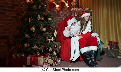 Little girl sitting on the lap of Santa Claus listening to...