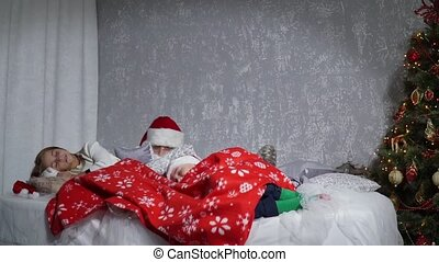 Santa sneaking up to sleeping babies on Christmas Eve