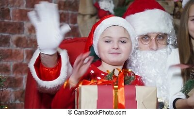 Closeup, happy children with gifts in hands waving together with Santa